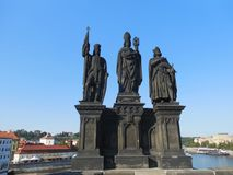 Historic statues on Charles Bridge in Prague,. The statues that stand on guard on Charles Bridge are some of the oldest in Prague attracting tourists to admire Royalty Free Stock Images