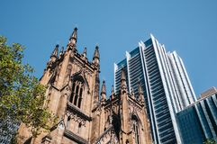 Historic stone gothic revival church building of St Andrew`s Cathedral next to urban high-rise towers in CBD. Historic stone gothic revival church building of stock photos