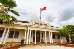 Historic stone National Treasury building, the centre of Nukualofa city. Red white cross tongan flag flying, Tongatapu, Tonga. stock photo