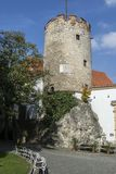 Historic stone round tower with white benches underneath it. In an ancient Moravian town Stock Photography