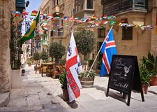 Historic streets Valletta decorated with flags. VALLETTA, MALTA - JUNE 24, 2018: Advertising banner in front of sports pub inviting to watch live football Stock Images