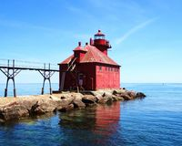 Historic sturgion bay Wisconsin lighthouse beautiful bright blue water and sky calm peaceful water wth reflection on water stock image