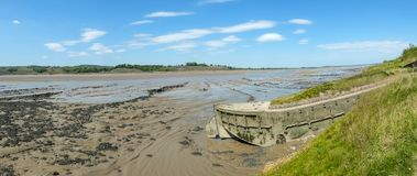 Historic tidal river bank erosion protection scheme at Purton Hulks, Gloucestershire, UK. Obsolete small boats and barges were stranded on the banks of the tidal royalty free stock photos