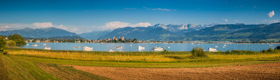 Historic town Rapperswil with Zürichsee at sunset, St. Gallen, Switzerland. Beautiful panoramic view of boats lying in Lake Zurich with the historic town of stock photography