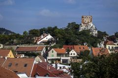A historic town with red roofs under a hill with a round stone tower Royalty Free Stock Photo