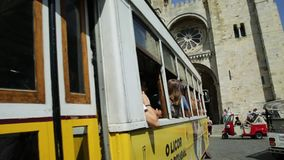 Historic tram and Lisbon Cathedral. Lisbon, Portugal - August 25, 2017: Historic tram 28 line in front of Lisbon Cathedral in Alfama district. Lisbon street with stock video footage