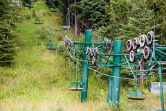 Historic two person ski lift. Old center pole 2 person chair lift surrounded by summer greenery at the Lutsen Ski Resort in northern Minnesota Stock Images