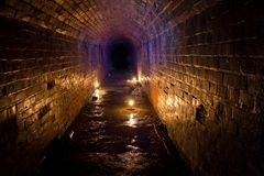 Historic underground passage under the abandoned fort. Illuminated by candles Royalty Free Stock Images