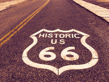 Historic US Route 66 highway sign on asphalt in Oatman, Arizona, United States. The picture was made during a motorcycle road trip. Through the south western Royalty Free Stock Photo