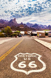 Historic US Route 66 with highway sign on asphalt and a panoramic view of Oatman, Arizona, United States. Royalty Free Stock Photo