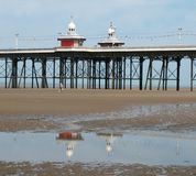 The historic victorian south pier in blackpool with the kiosks reflected in the pools on the beach. A view of a section of the historic victorian south pier in stock photos