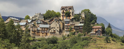 Historic village in the Alps no.1. Old historic village on a hill in the French Alps with clouds and mountains in the background Stock Photos