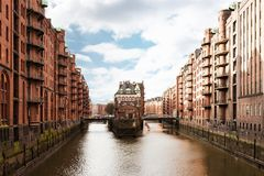 Historic warehouse district Speicherstadt in Hamburg, Germany. Canal in historic warehouse district Speicherstadt in Hamburg, Germany under partially clouded sky Stock Photography