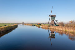 Historic watermill reflected. Dutch polder landscape in autumn with an old windmill with scoopwheel next to a small river Royalty Free Stock Image