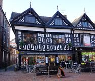 Historic Wattle And Daub Building, Nantwich, Cheshire, England. NANTWICH, UK - DECEMBER 29 2015: Pedestrians sit in an outdoor dining area outside a small Stock Images