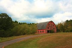 Historic, weathered old barn on a hill. Scenic Western Wisconsin, historic old weathered red barn on a hill with trees in background and blue sky Stock Photo