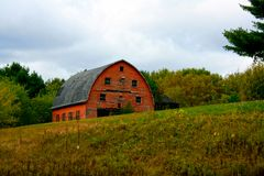 Historic, weathered old red barn on a hill. Scenic Western Wisconsin, weathered old red barn on a hill, farm, cloudy Stock Photography