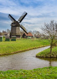 Historic windmill next to canal in Holland Stock Photography