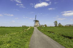 A historic windmill in Nieuwe Wetering. A road to a historic windmill in the green fields and a blue cloudy sky of Nieuwe Wetering in The Netherlands royalty free stock photo