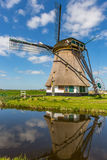 A historic windmill with reflection on the water. A historic windmill with reflection on the water in the green fields and a blue cloudy sky of Rijpwetering in royalty free stock photography