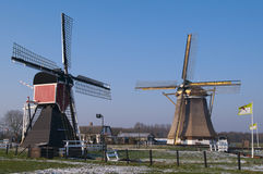 Historic windmills against a winter sky. Two historic dutch windmills against a winter sky in a meadow covered with hoarfrost Stock Images