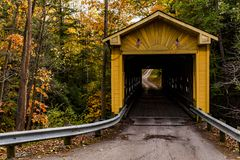 Historic Windsor Mills Covered Bridge in Autumn - Ashtabula County, Ohio. A scenic view of the historic yellow hued Windsor Mills Covered Bridge bathed in autumn royalty free stock image