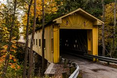 Historic Windsor Mills Covered Bridge in Autumn - Ashtabula County, Ohio. A scenic view of the historic yellow hued Windsor Mills Covered Bridge bathed in autumn stock images