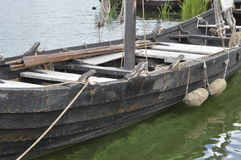 Historic wooden boat. Wolin, Poland: Historic wooden boat submerged in greenish water Stock Images