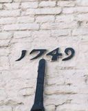 Historic Writing. Old historic datestone on a buiding: The date 1749 painted black, and set in a white- washed brick wall Stock Photos