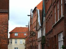 Historical alley with redbrick houses with any guild signs and lanterns at a rainy day royalty free stock photography