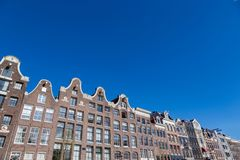 Historical Amsterdam canal houses on a blue sky. A clear blue sky over the historical canal houses on the Prinsengracht in the center of Amsterdam in the stock image