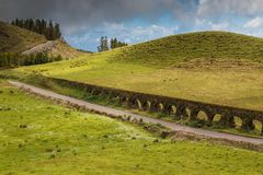 Historical aqueduct at Sao Miguel, Azores Islands. Green spring fresh fields. Road lined by historical aqueduct. Hills and trees in the background. Cloudy sky stock images