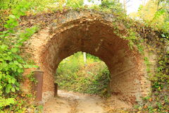 Historical arch from ed bricks in Kachanivka park. Sandy road under historical arch from ed bricks in Kachanivka park Stock Photos