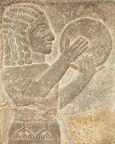 Historical Assyrian relief of musician with drum playing traditional music Royalty Free Stock Photo