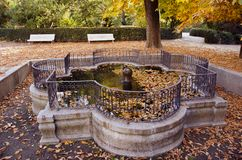 Historical beautiful fountain in old city park with bench in autumn Stock Photos