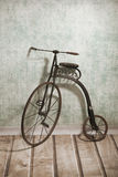 Historical bicycle by the wall. Historical children's high-wheel bicycle Royalty Free Stock Photos