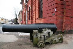 Historical building of red brick in Kronstadt, Russia with the vintage gun in front in winter cloudy day Royalty Free Stock Photos