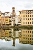 Historical buildings with bell tower mirrored in the river Arno, Stock Photos