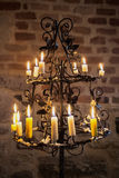 Historical candlestick with a burning wax candles. In front of a brick wall Catholic church basement Stock Photo