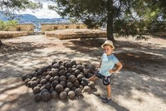 Historical cannonballs. The Historical cannonballs  in old Venetian fortress of Rethymnon in Crete, Greece . Europe . And young boy Royalty Free Stock Photo