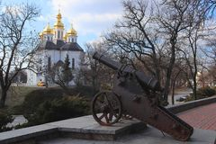 The historical center of the ancient Ukrainian city of Chernigov. Old cannon on the rampart. Beautiful white church with golden do stock images