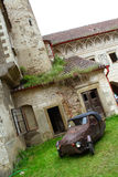 Historical corner. Old three-wheeled car on the court of the abandoned castle stock photo