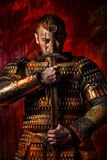 Historical fantasy. Portrait of a courageous warrior wanderer in a black cloak and sword in hand. Historical fantasy Royalty Free Stock Photos