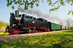 Historical German steam train in spring. Historical German steam train passes through the fields Royalty Free Stock Images
