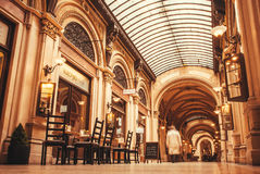 Historical hall with walking people, shops and outdoor cafe tables Royalty Free Stock Photos