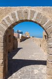 Gate in the fortification, El Jadida, Morocco. Historical heritage, former portuguese fortress. Gate with an arch, made of stones. In the background building of royalty free stock image
