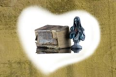 A historical holy bible and a Madonna sculpture are enclosed by stock photos