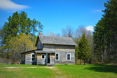 Historical Home. This is the Historical Rankinen Farm and House at Old World Wisconsin framed by evergreen trees and the shadows on the grass Stock Image