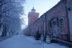 Historical jetty barracks and clock tower on cold winter morning in Suomenlinna fortress island. Royalty Free Stock Photos