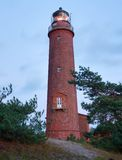 Historical lighthouse. Shinning lighthouse,  dunes and pine tree. Tower illuminated. With strong warning light, dark sky in background. Lighthouse tower built Stock Images